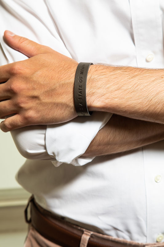 Man wearing brown wristband with a message