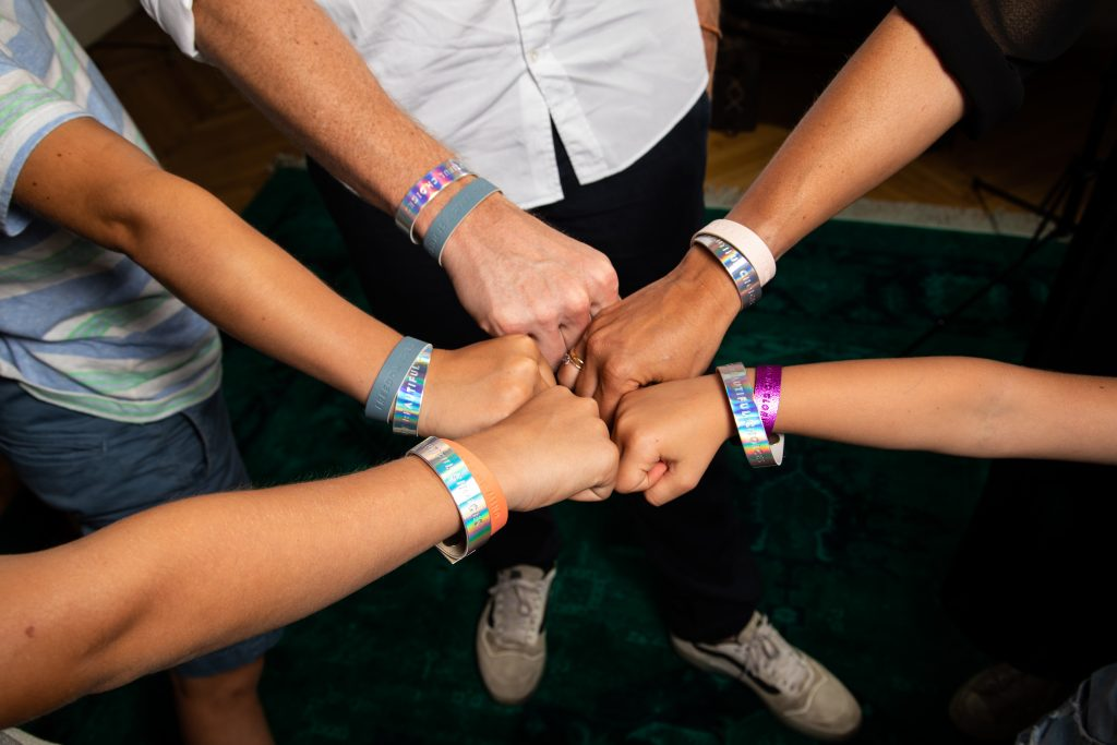 A team showing their wristbands with a message