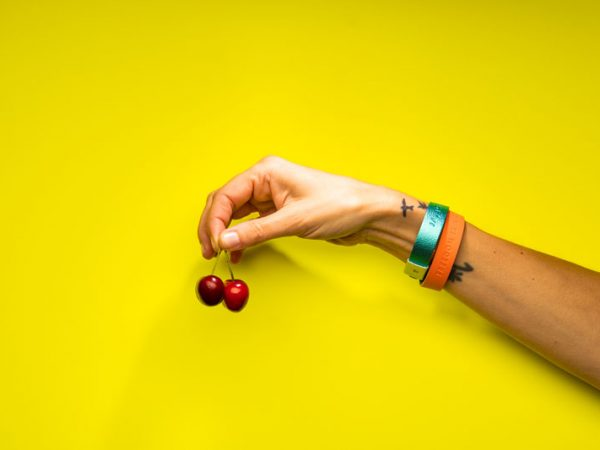 Wristbands with a message on a hand holding cherries