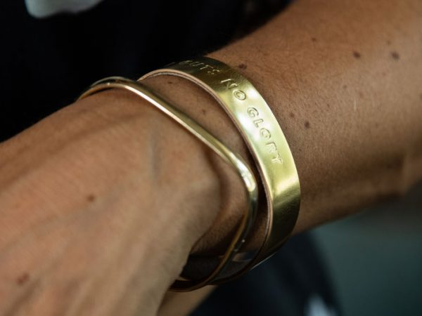 Gold wristband with a powerful message on hand