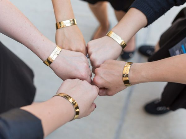 Team wearing gold wristbands with the same message