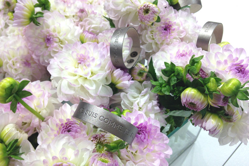 Silver metallic wristbands with the message Je suis comme je suis on flowers